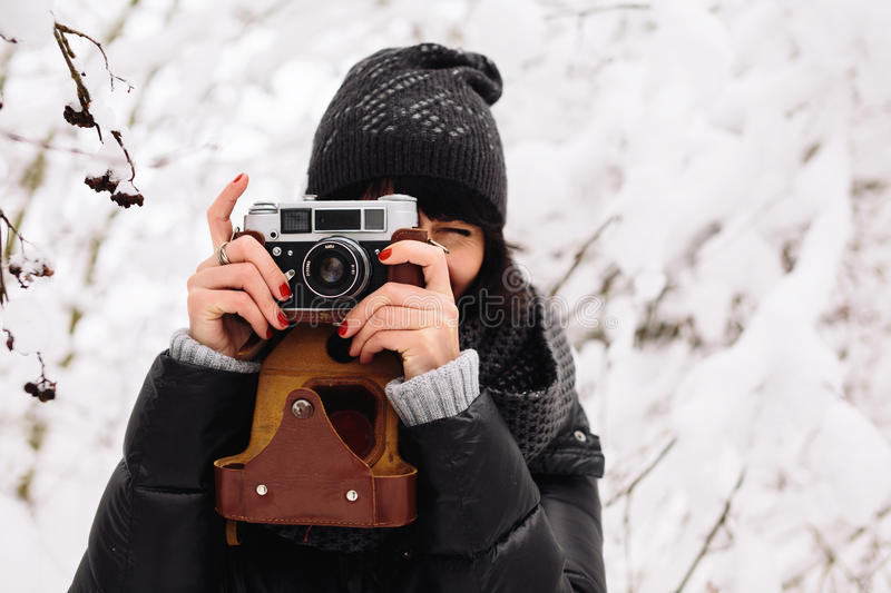 Smiling girl photographed on a camera in winter royalty free stock photos