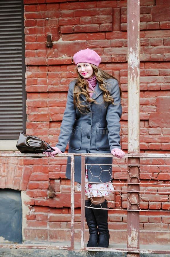 Smiling girl in pink beret posing on city street stock photos
