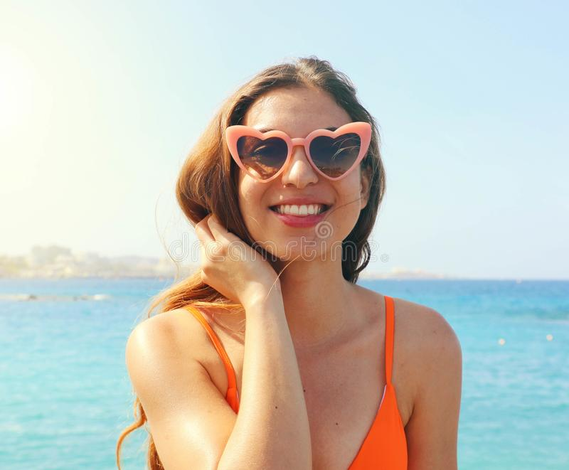 Smiling girl in pink heart lolita sunglasses on the beach. Holidays, vacation travel and freedom concept royalty free stock photo