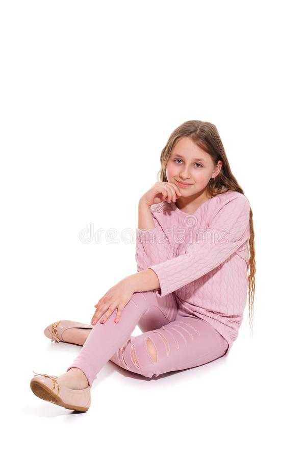 A smiling girl in a pink suit is sitting on the floor. Isolation on a white. royalty free stock photo