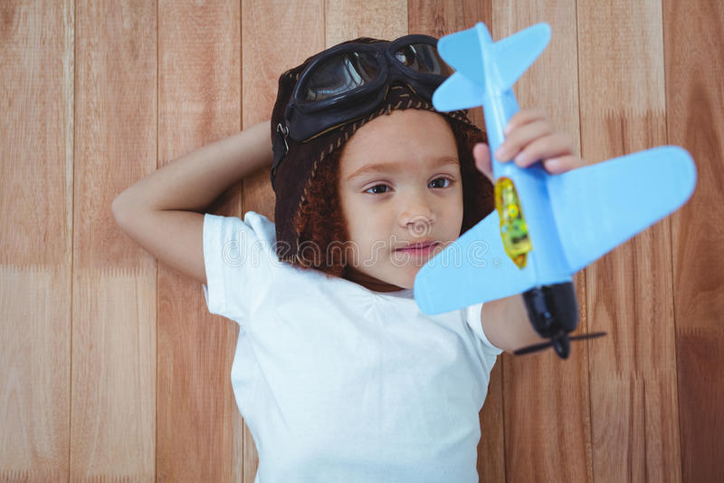 Smiling girl playing with toy airplane. Smiling girl laying on the floor playing with toy airplane stock photography