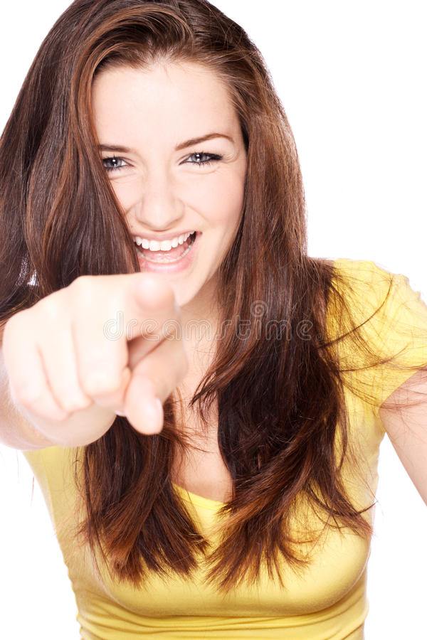 Smiling girl pointing. A beautiful young woman smiling and pointing at the camera stock photo