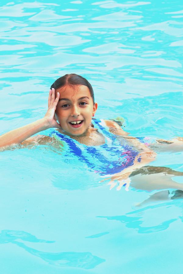 Smiling Girl in Pool Shows Off Floating Skills in Summer Fun stock photos