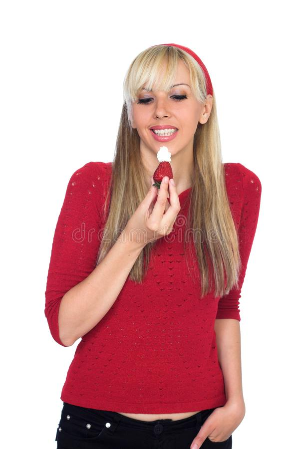 Smiling girl preparing to eat strawberry with whipped cream stock image