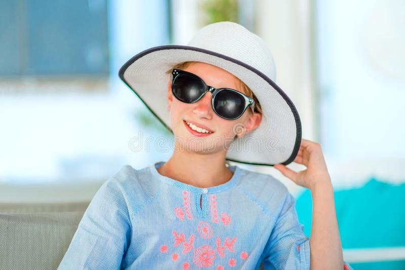 Smiling girl in a pretty white hat and light blue blouse royalty free stock images