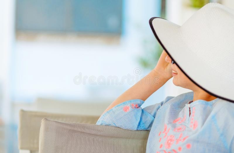 Smiling girl in a pretty white hat and light blue blouse royalty free stock photography