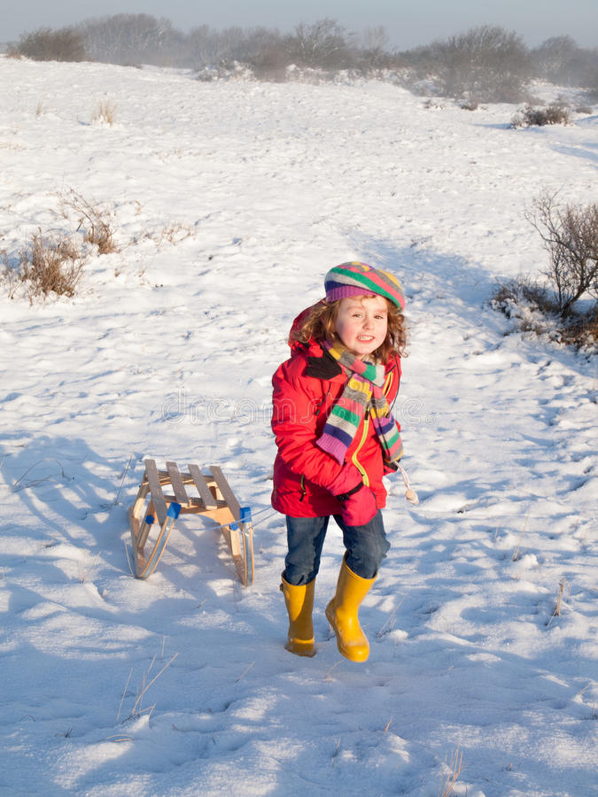 Smiling girl pulling a sledge stock images