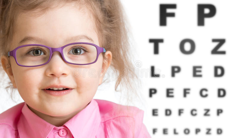 Smiling girl putting on glasses with blurry eye royalty free stock images
