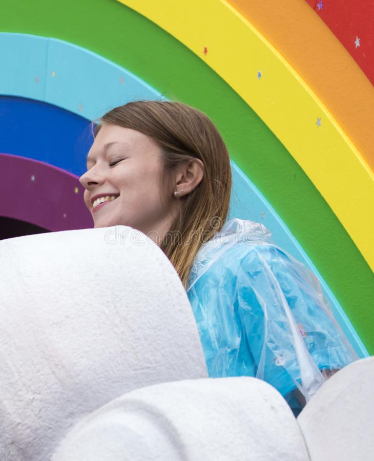 A smiling girl with a rainbow behind her attending the Gay Pride parade also known as Christopher Street Day CSD in Munich. 2019: A smiling girl with a rainbow royalty free stock photography