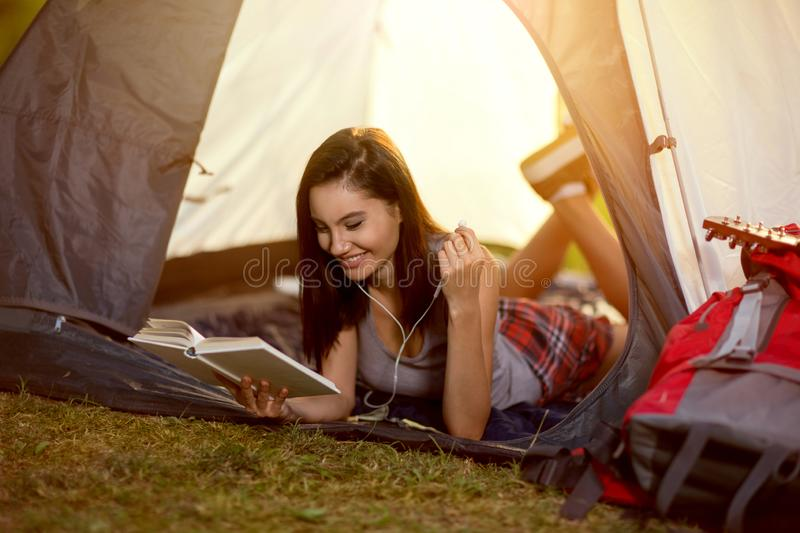 Girl reading a book in tent on camping stock images