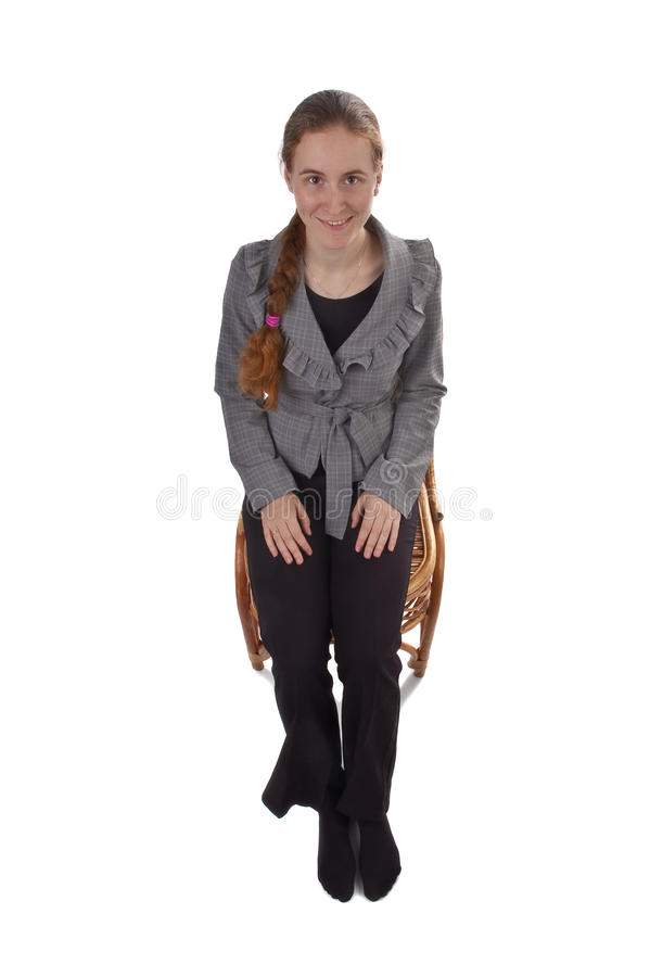 Smiling girl with red braid sitting on the chair stock photos