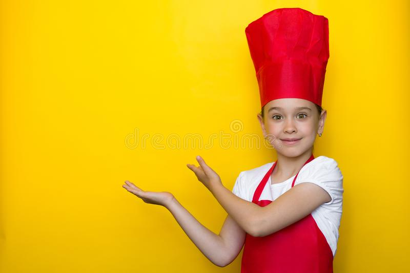 Smiling girl in a red chef`s suit points with both hands to a copy space on a yellow background royalty free stock photos