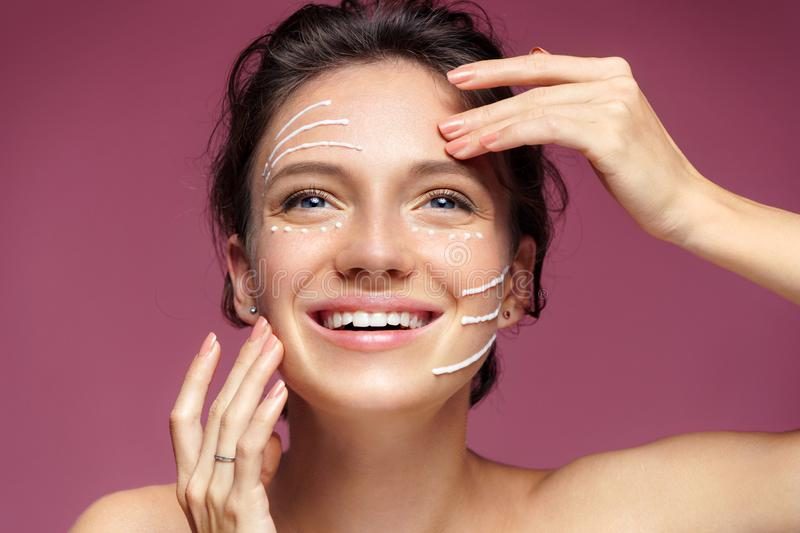 Smiling girl with rejuvenating cream on her face stock photo
