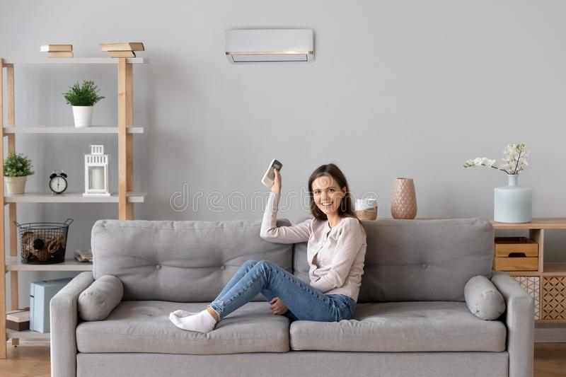 Smiling girl relax on couch turn on air conditioner royalty free stock image