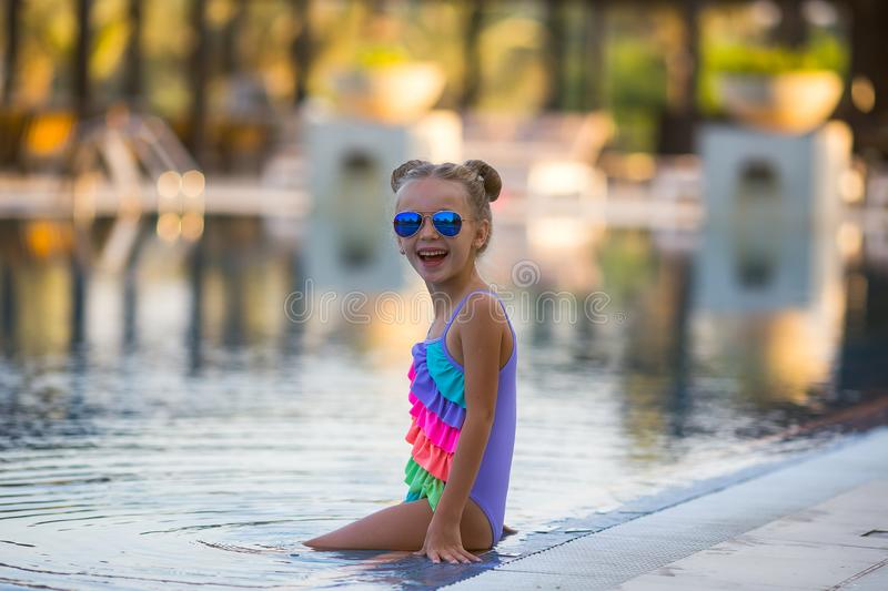 Beautiful girl in a swimsuit swims in the pool by the summer. royalty free stock images