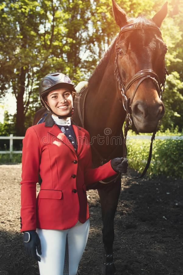 Smiling Girl rider and a horse posing in spring forest. looking into the camera. A young girl takes care of her horse. She loves the animals and joyfully spends stock photo