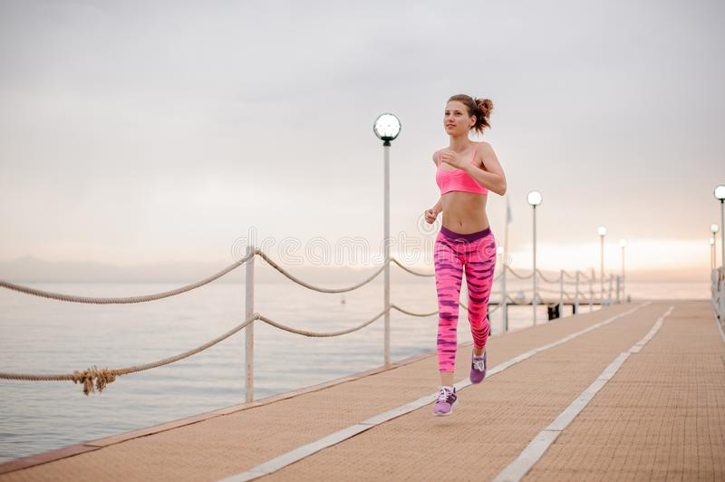 Smiling girl running to the new life on the sunrise. Ready to achieve a new goal.Conception of the healthy lifestyle stock photo