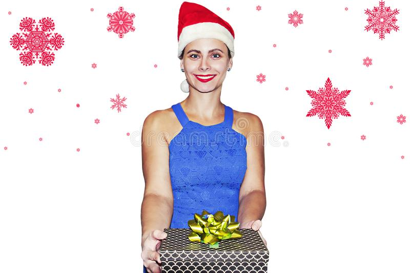 Smiling girl in Santa Claus hat with gift box in hand on white background with red snowflakes stock images
