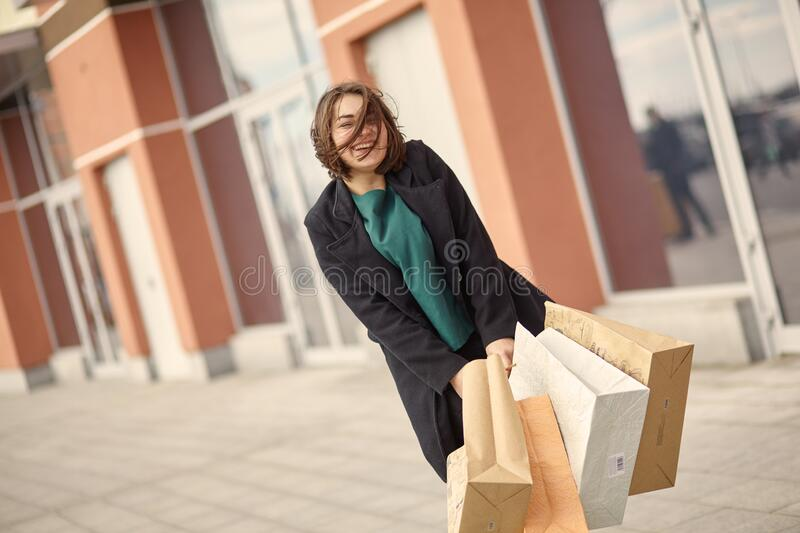 Smiling girl with shopping bags in a city stock images
