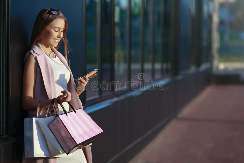 Smiling girl with shopping bags and looking in the phone royalty free stock photo