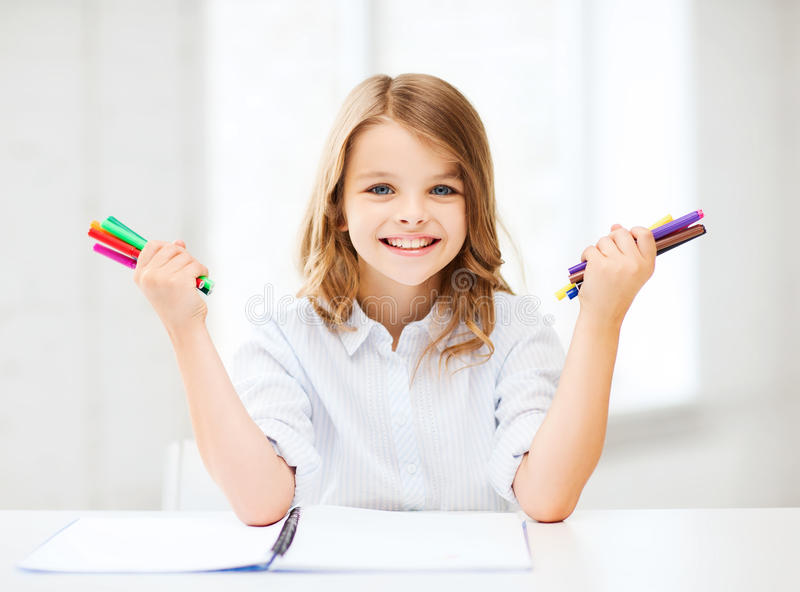 Smiling girl showing colorful felt-tip pens. Education, creation and school concept - smiling little student girl showing colorful felt-tip pens at school royalty free stock image