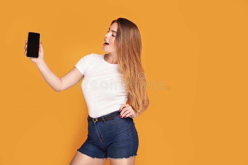 Smiling girl showing mobile phone with empty screen. Studio shot of attractive redhead young woman stands smiling and showing mobile phone with empty screen royalty free stock image