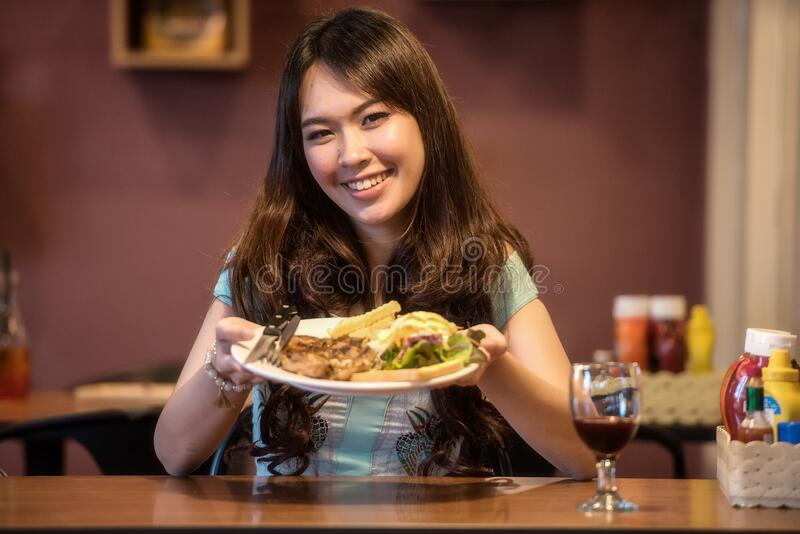 Smiling girl shows her plate of food stock photography
