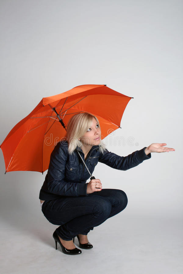 Smiling girl siting under umbrella stock image