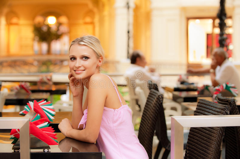 Smiling girl sits at little table at restaurant royalty free stock images