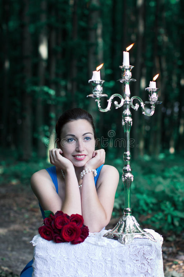 smiling girl sits at a table with a bouquet of red roses and silver candlestick in a forest royalty free stock image