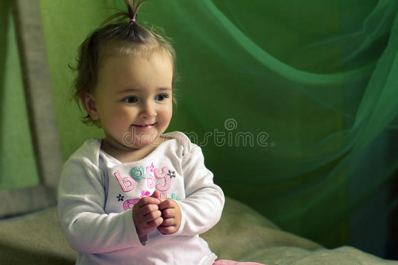 Smiling girl sitting on the bed royalty free stock images