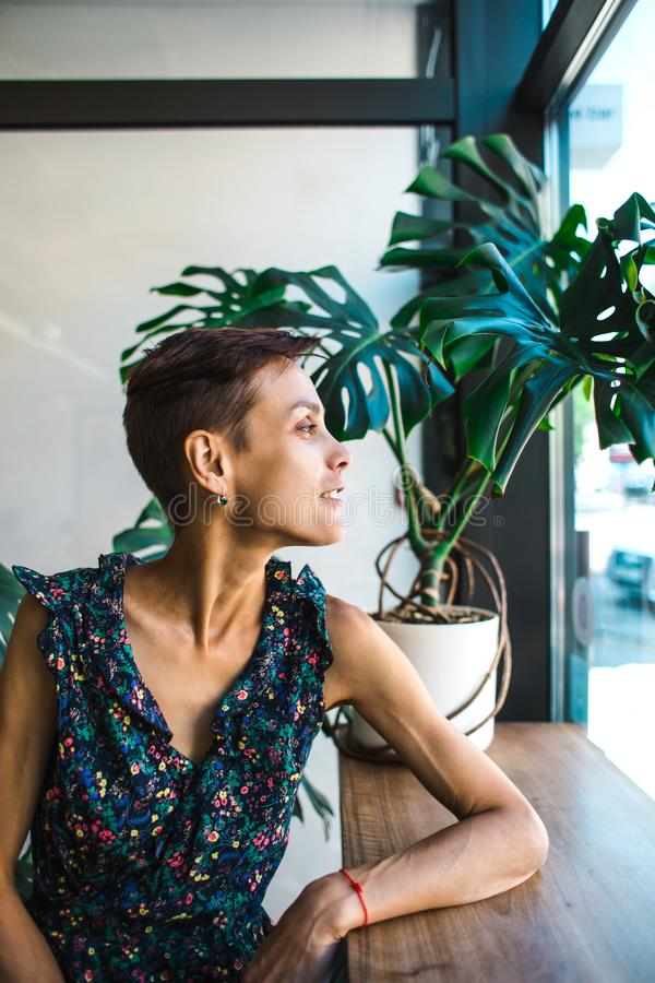 Smiling girl sitting in a coffee shop and looking out the window stock photo
