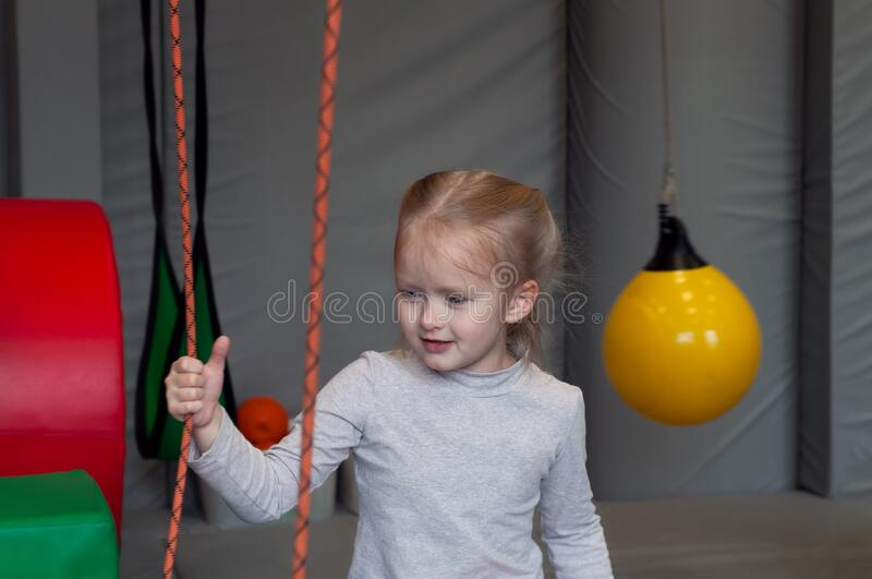 Smiling girl sitting in gym sensory integration. On background royalty free stock image