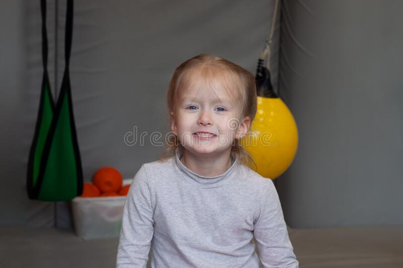 Smiling girl sitting in gym sensory integration. On background royalty free stock photo