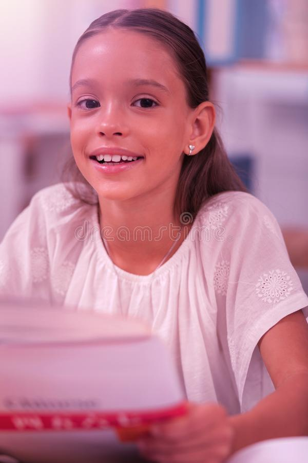 Smiling girl sitting at the school desk. Happy childhood. Smiling pretty girl sitting at the school desk holding a foreign language workbook stock photos