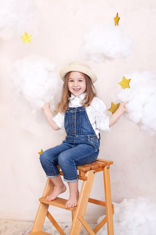 Smiling girl sitting on the stairs in the sky with clouds and with the stars. Little astrologer Little traveler. The girl flies in stock images