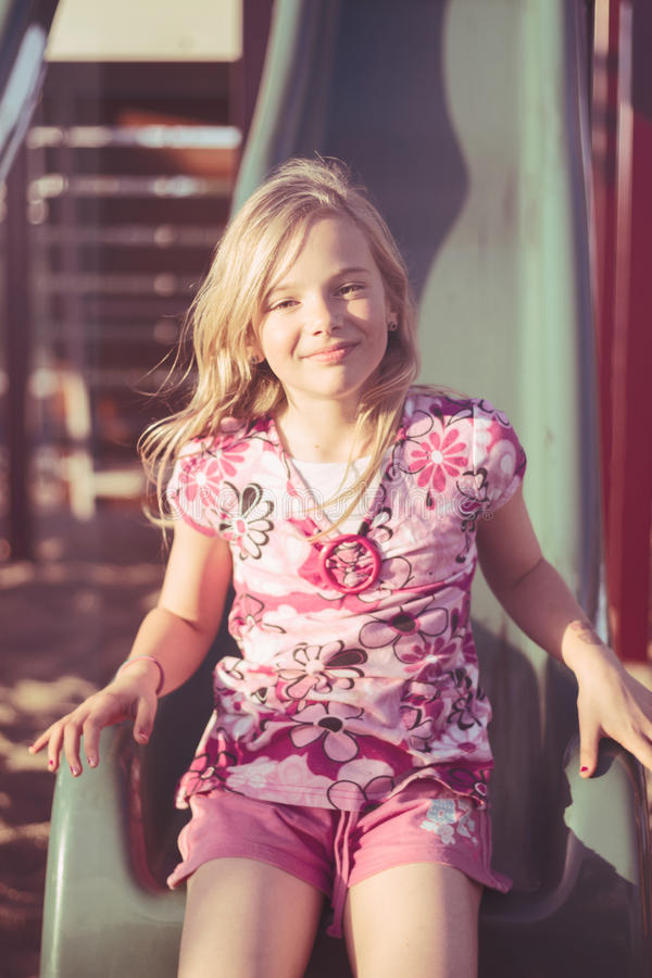 Smiling girl on slide royalty free stock photography