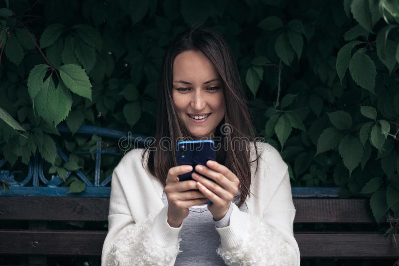 Smiling girl with smartphone in her hands sitting on bench in Park stock image