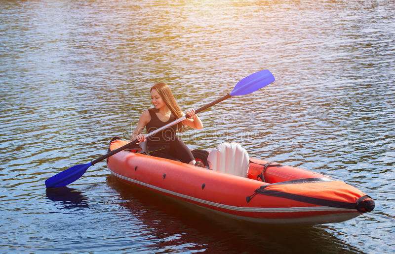 The smiling girl -the sportswoman with long,dark hair in black,sportswear rows with an oar on the lake in a red, inflatable canoe. In a warm,summer,sunny day stock photography