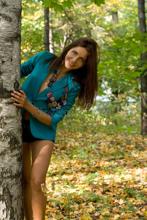 Smiling girl standing near birch stock photography