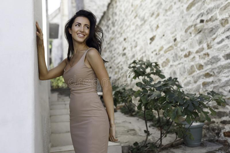 Smiling girl standing near the old stone wall. Beautiful woman with long hair posing sexy outside in holiday in Greece. royalty free stock photos