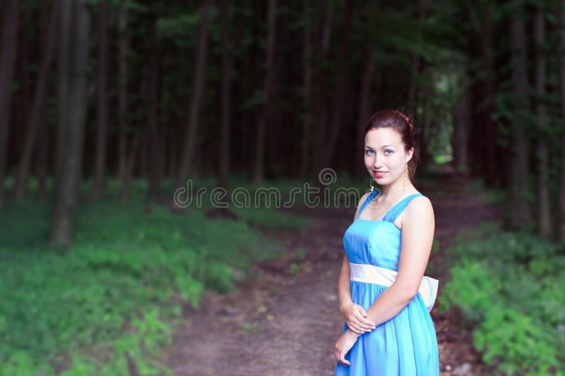 Smiling girl stands on a footpath of dark forest royalty free stock photography