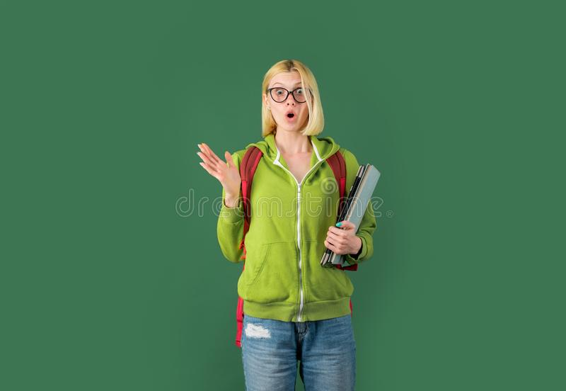 Smiling girl student or woman teacher portrait on green wall blackboard background. College student at campus. Happy royalty free stock photography