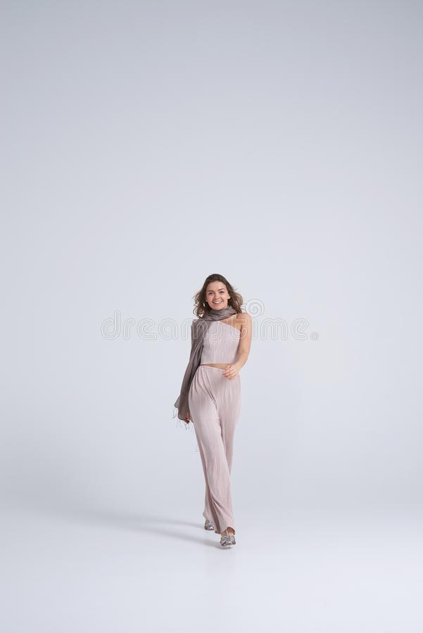 Smiling girl in stylish clothes walking towards camera royalty free stock photos
