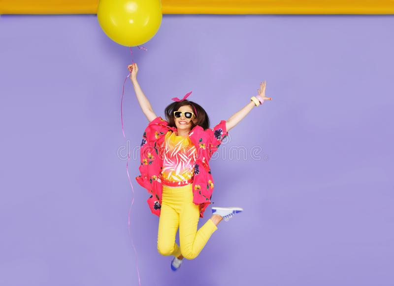 Smiling girl in sunglasses, jumping, holdiing a big balloons, isolated on violet background. Space for text. royalty free stock images
