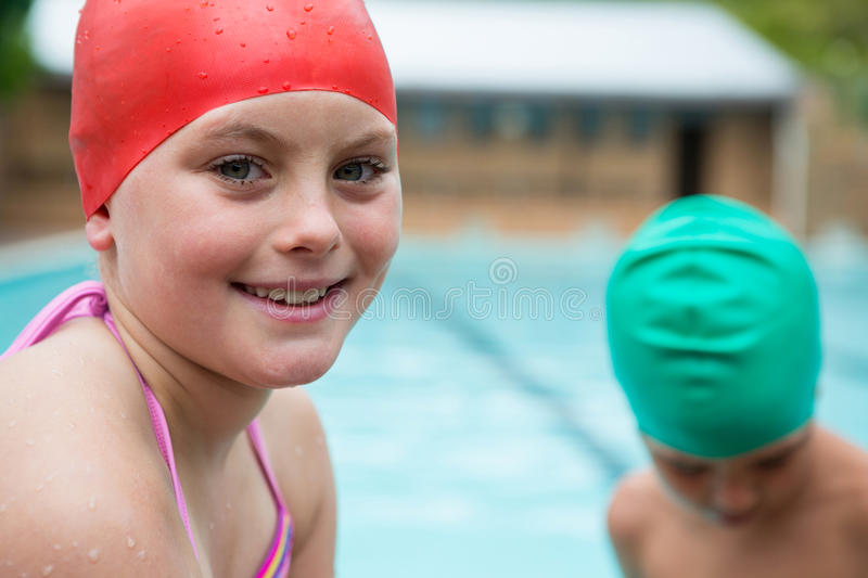 Smiling girl with swim cap near poolside. Portrait of smiling girl with swim cap near poolside royalty free stock photography
