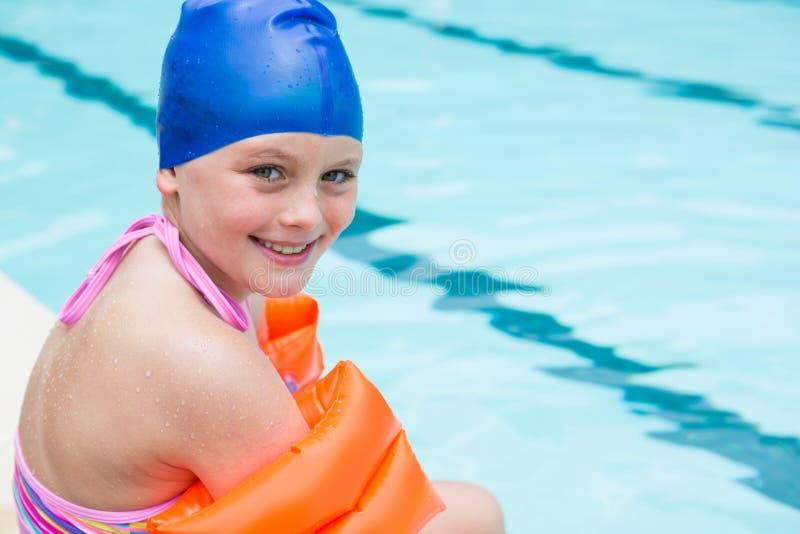 Smiling girl with swim cap sitting near poolside. Portrait of smiling girl with swim cap sitting near poolside royalty free stock photo