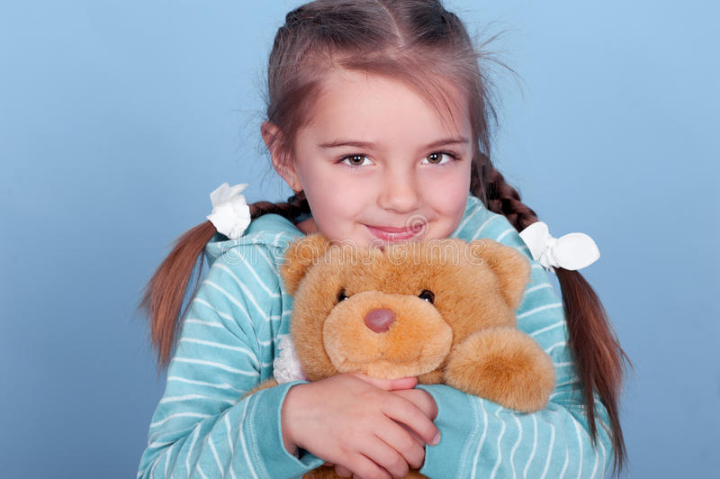 Smiling girl with teddy bear royalty free stock photography