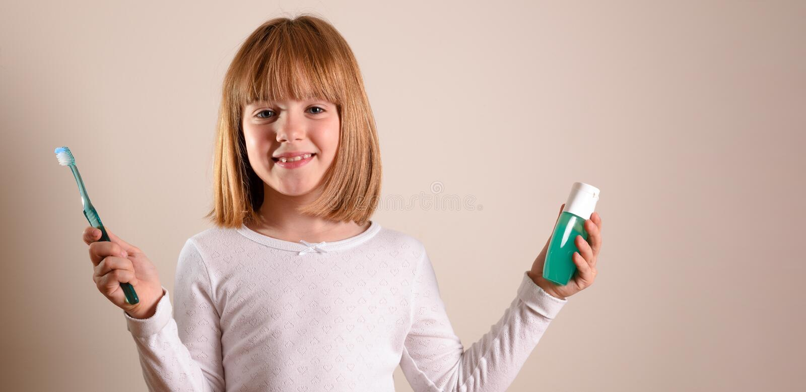Smiling girl with toothbrush and toothpaste on isolated brown royalty free stock image
