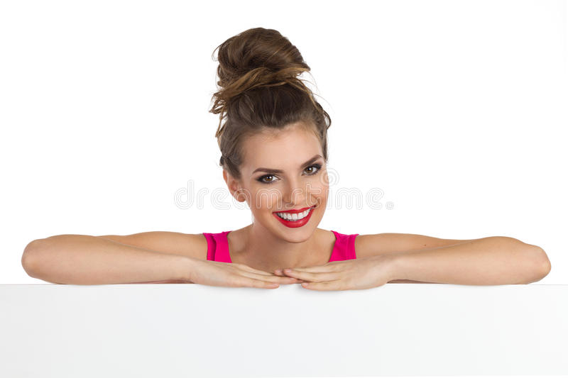 Smiling Girl With A Topknot. Beautiful smiling young woman with big hair bun leans on a white banner and looking at camera. Head and shoulders studio shot stock images